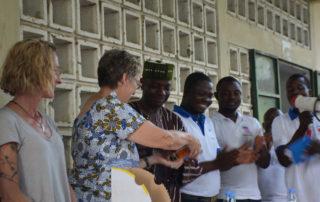 Wir übergeben Babynahrung und Moskitonetze an den Dorfchef vor der Bevölkerung.