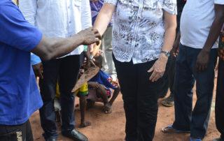 Margret Kopp von Aktion PiT - Togohilfe darf eine Kelle schaufeln und gibt die Kelle an den Dorfchef weiter.