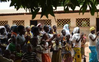 Die Dorfbevölkerung kommt trommelnd, klatschend, singend und tanzend zum Empfang.