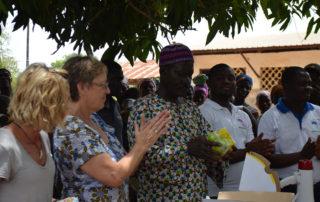 Wir übergeben Babynahrung und Moskitonetze vor der Bevölkerung an den Dorfchef.