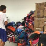 Unsere fleißigen Helfer tragen die Schultaschen zum Container
