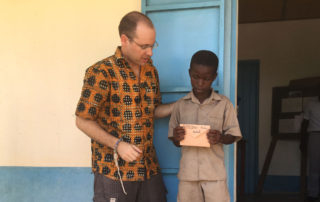 Andy Kopp trifft eines der Patenkinder in Kouma Apoti, Togo, Afrika