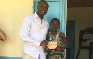 Dr. Michel Kodom von Aimes-Afrique trifft eines der Patenkinder in Kouma Apoti, Togo, Afrika