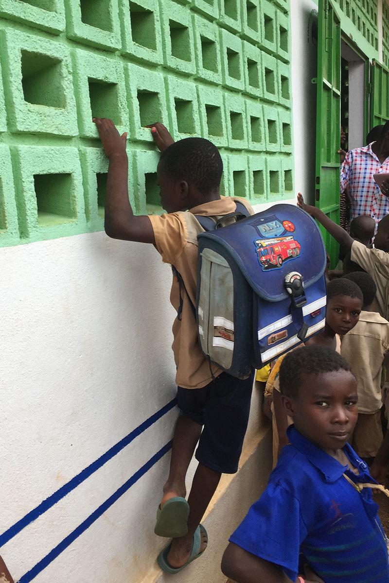 Ein Kind in Togo trägt eine gespendete Schultasche am Rücken.
