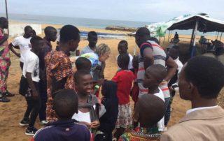 Margret Kopp umringt von Kindern und Jugendlichen am Strand von Lomé