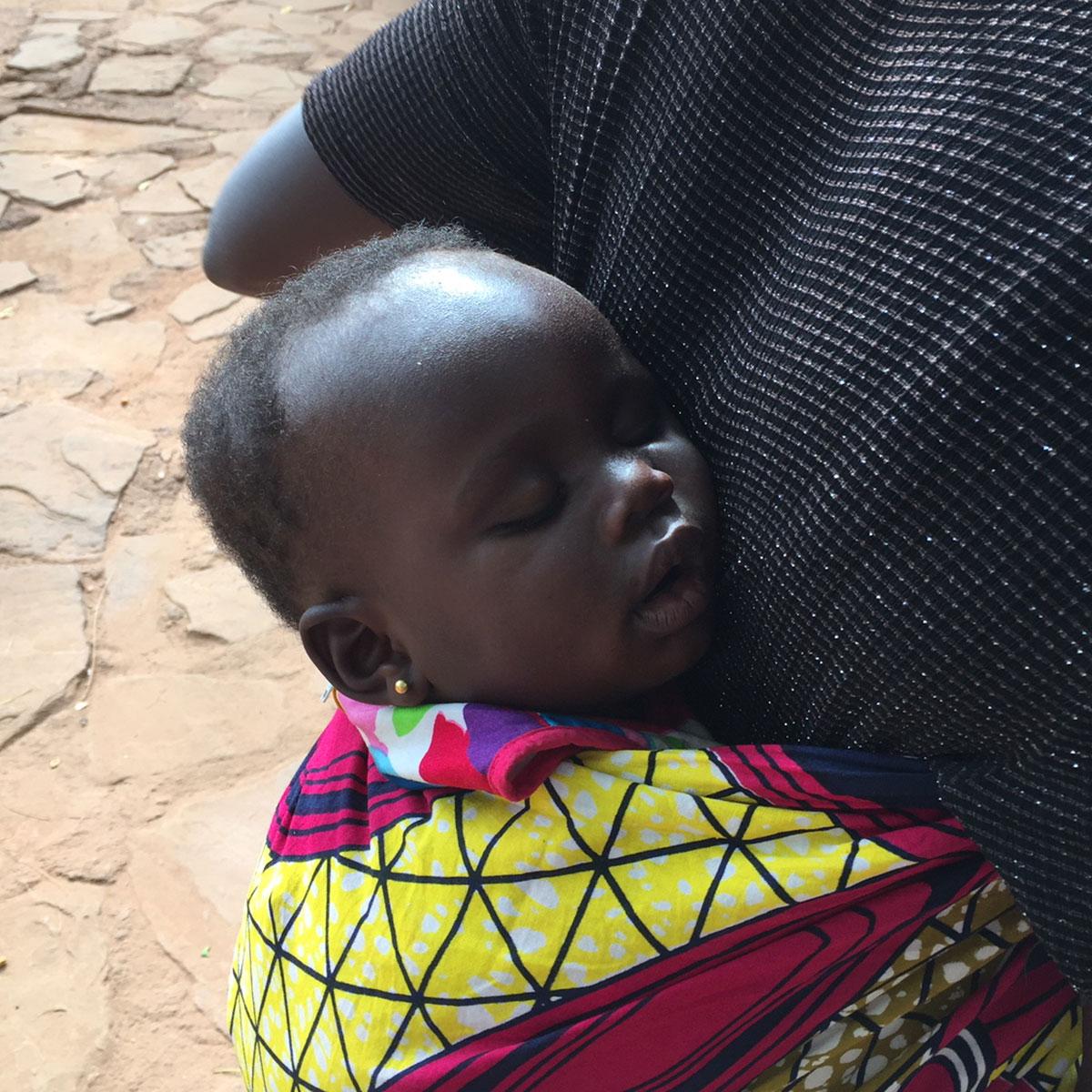 Die kleine Lea schlummert entspannt auf dem Rücken ihrer Mama