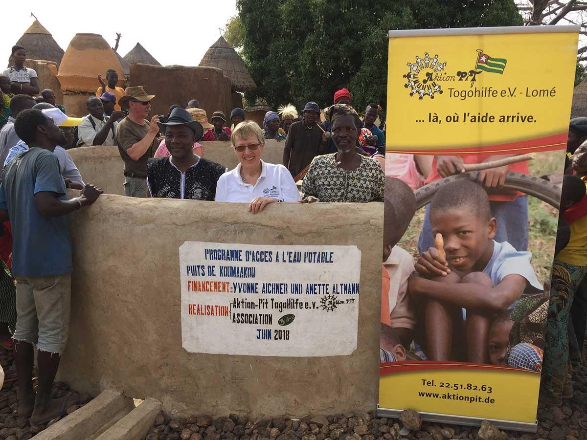 Der Brunnen mit Schild des Spenders v.l.: Mr. Kouagou (unser Partner vor Ort), Margret Kopp, der Dorfchef