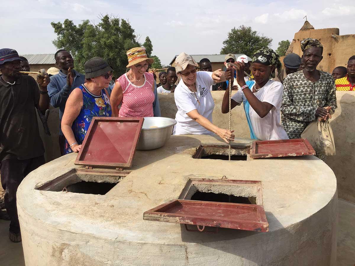 Wir schöpfen mit Hilfe der Frauen frisches Wasser aus dem neuen Brunnen