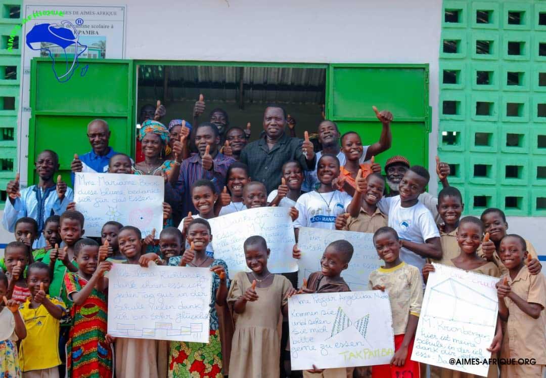 Eine Gruppe von Kindern zeigt Schilder mit Dank an Aktion PiT