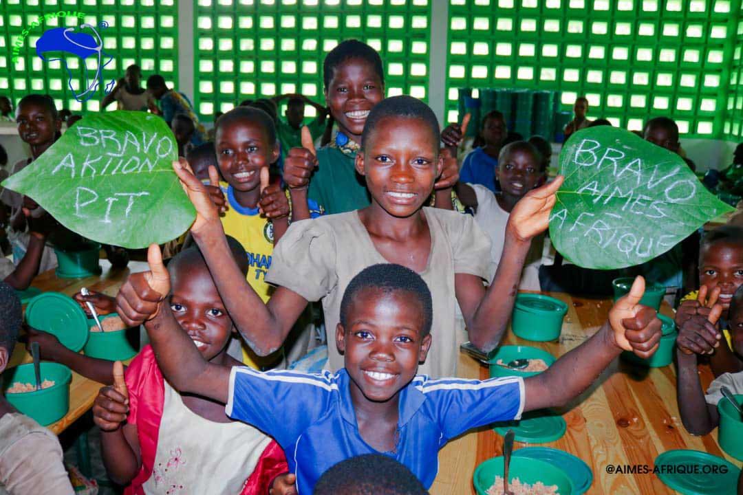 Lachende KiSS-Kinder halten Blätter mit Bravo Aktion PiT und Bravo Aimes-Afrique in den Händen