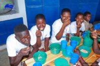 Fröhliche Kinder beim essen der Schulspeisung