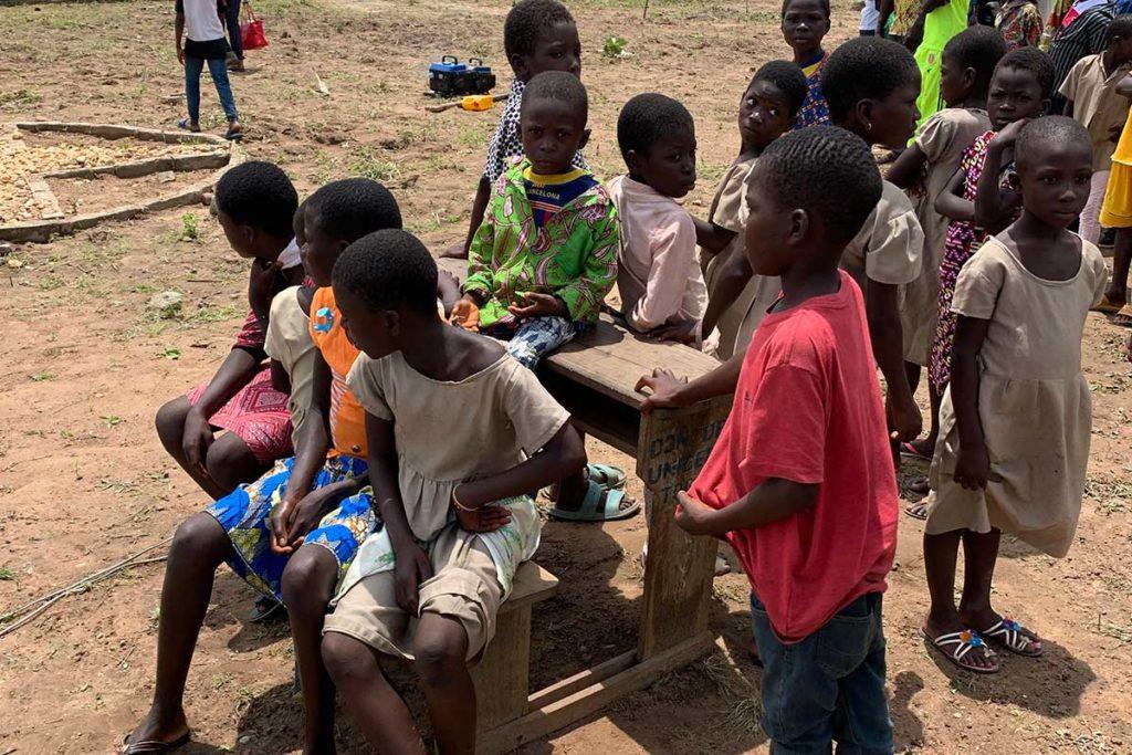 Kinder sitzen während der Einweihungsfeier draußen