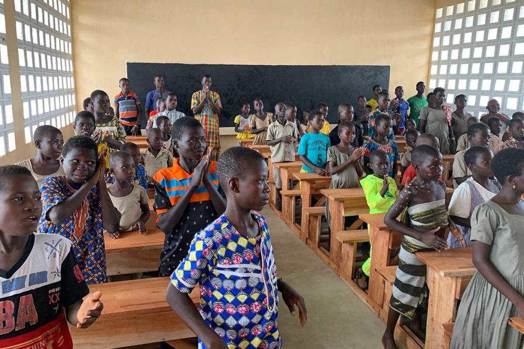 Die Schüler sitzen in der neuen Schule an Ihren neuen Tischen