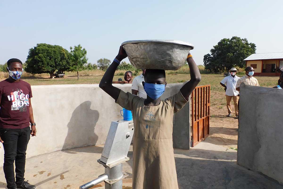 Eine Schüler aus Djabagbal trägt eine Schüssel voll Wasser