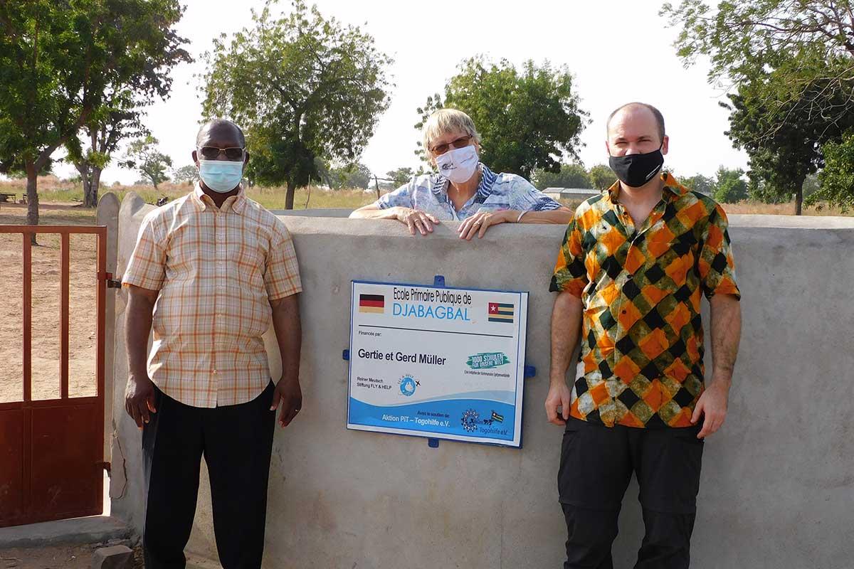 André Buegem, Margret Kopp und Andy Kopp vor dem Brunnen in Djabagbal