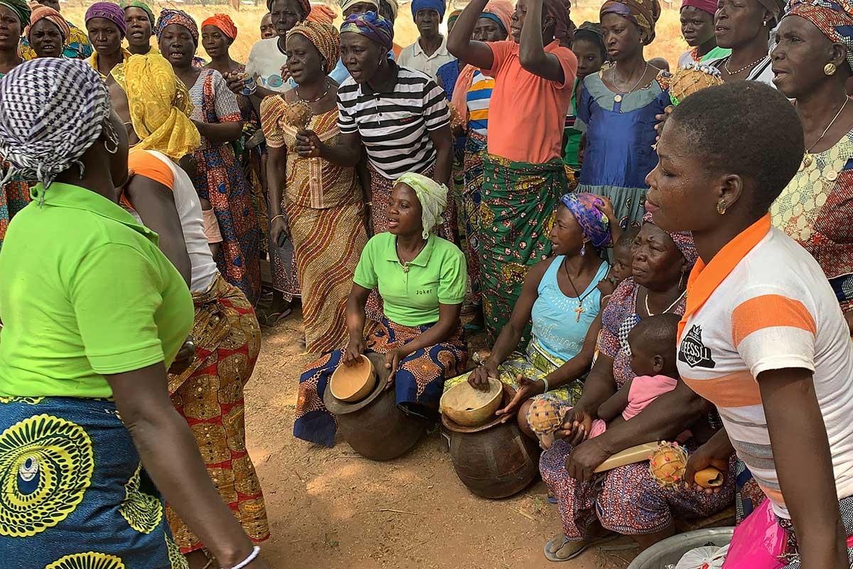 Die Frauen begrüßen uns mit Tanz, Gesang und einer nur hier üblichen Art des Trommelns: Kalebassen werden auf Tonkrüge geschlagen.