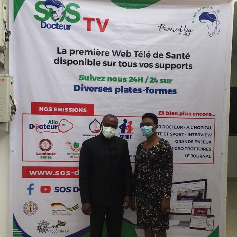 """Dr. Kodom mit Elbine Ditoma vor dem großem """"SOS Docteur TV""""-Banner"""