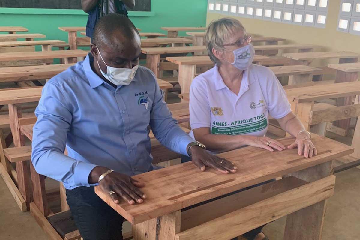 Dr. Michel Kodom und Margret Kopp sitzen in einer Schulbank